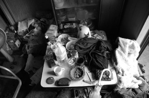 A table full of Watanabe's abandoned possessions, cigarettes and half-eaten food. The room is littered with these shrines to domestic irresponsibility.